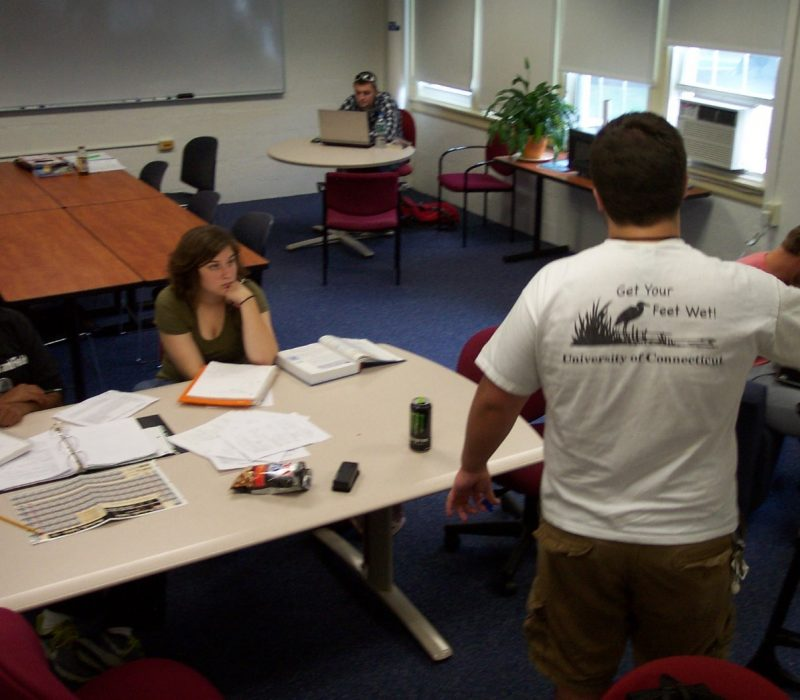 A tutor explains Chemistry in a group tutoring session.