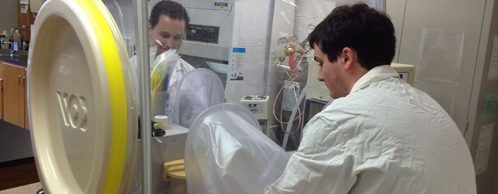 Microbial Systems Analysis students use the anaerobic chamber during the operations of a microbiology laboratory module