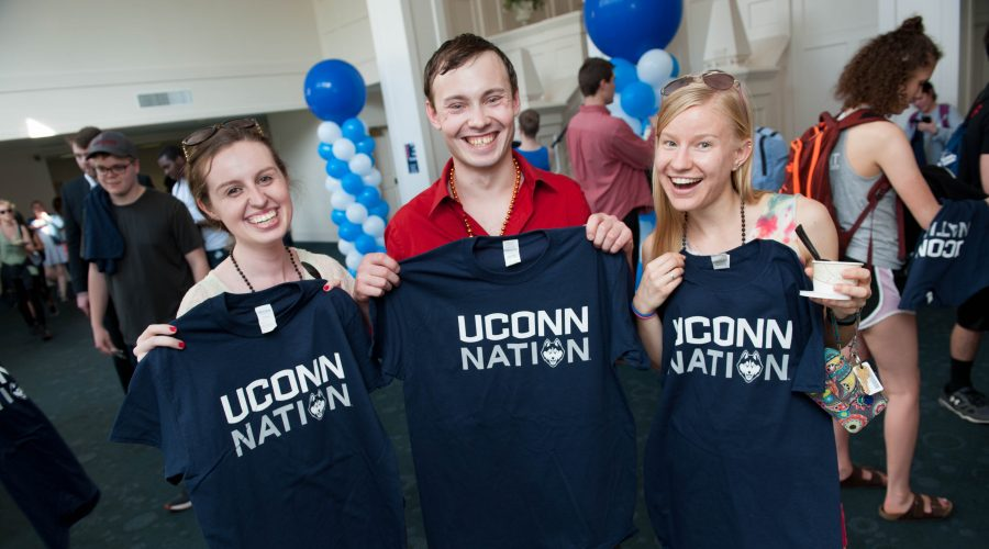 Three seniors smiling while holding UConn Nation t-shirts