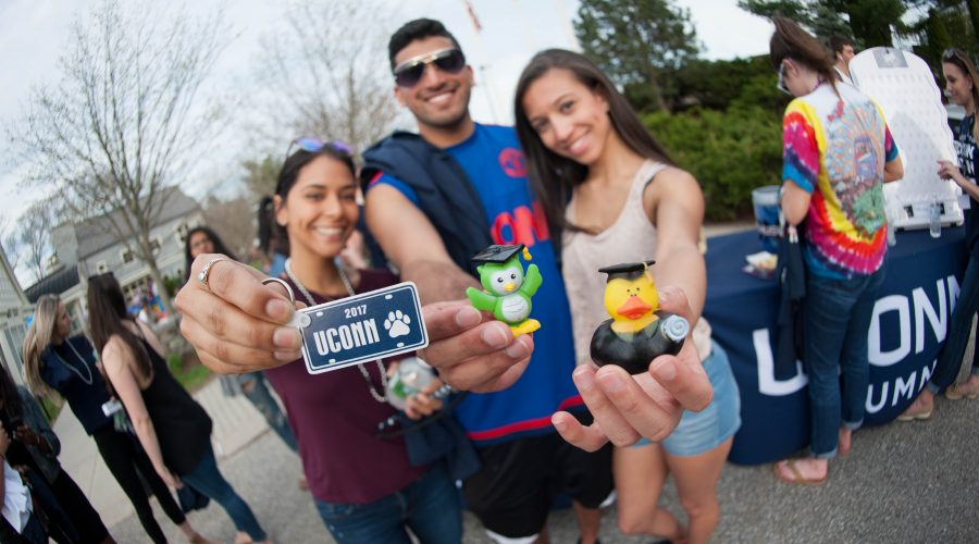 Three seniors holding a UConn 2017 keychain, a graduation owl figurine, and a graduation rubber duck