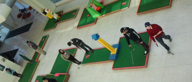 Students playing mini-golf on the concourse