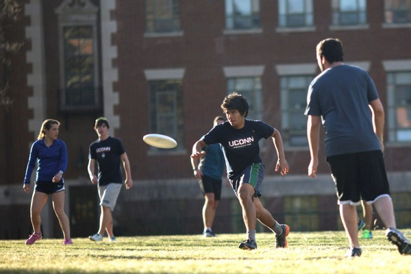 UConn students playing frisbee outdoors